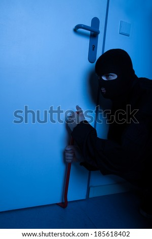 Thief opening door with crowbar during house breaking - stock photo