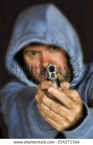 Thief or gang member holding a handgun in a threatening position - stock photo