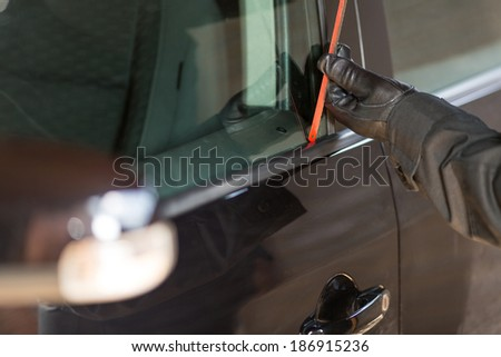 Thief picking the lock of a car parked on the street - stock photo