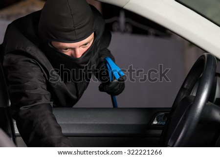 Thief preparing to steal a parking car at night. - stock photo
