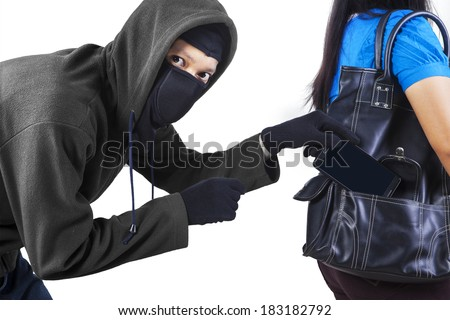 Thief stealing a mobile phone from handbag of a woman isolated on white - stock photo
