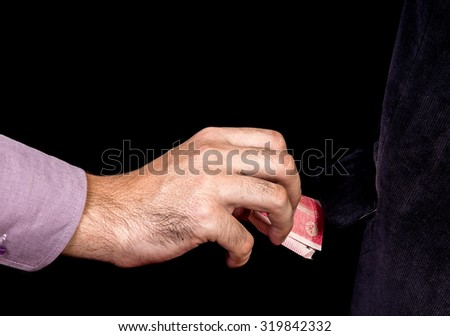 thief stealing money by reaching his hand picking up 5000 banknote from coat pocket  isolated with black background - stock photo