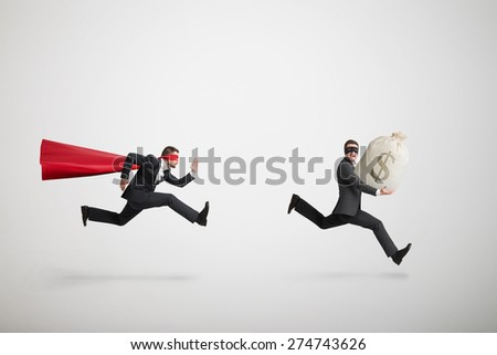 thief stole the bag with money and running away from superman over light grey background - stock photo