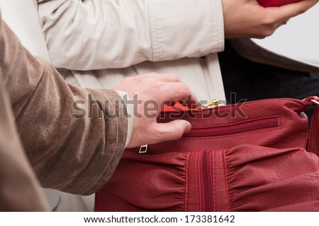 Thief trying to take out the wallet from lady's purse - stock photo