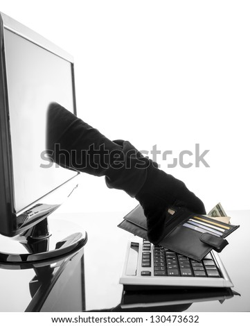 Thief with glove stealing wallet through a computer screen. Concept of internet crime. - stock photo