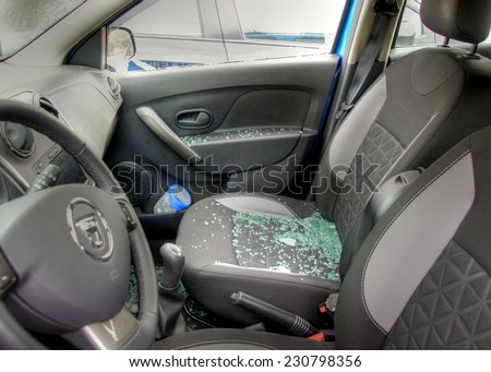 Thiefs have broken a car window to steel items inside  and the glass is spread all over the car seats  - stock photo