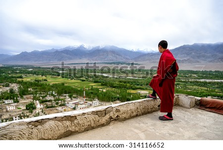 Thiksey, Ladakh - August 24, 2015: View of young monk on Thiksey gompa roof. Thiksey monastery is located on top of a hill in Thiksey village, approximately 19 kilometres east of Leh in Ladakh, India  - stock photo