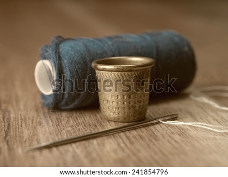 thimble and needles for sewing close-up on a background thread spools. macro - stock photo