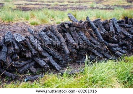 Thin blocks of cut peat dries in piles in wet upland rural Ireland - stock photo