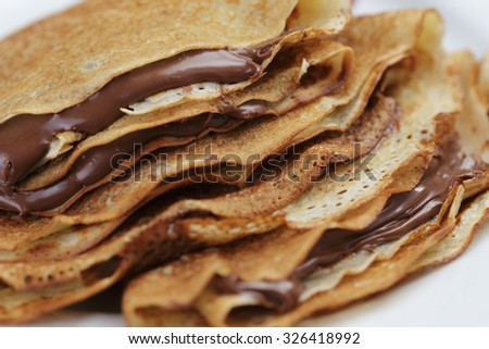 thin crepes or blinis with chocolate cream close up