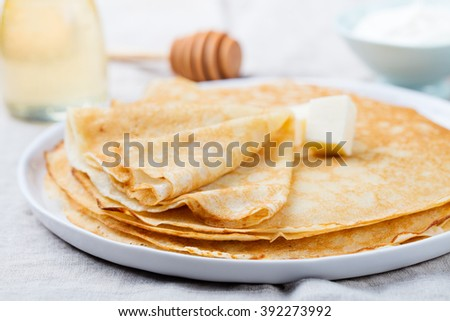 Thin crepes or pancakes with butter, honey and sour cream on a rustic textile background