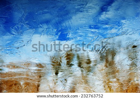 Thin ice crust covers the calm water. The sky with clouds and autumn shore are reflected in the frozen water surface.