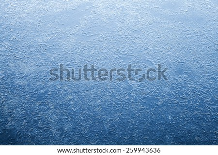 Thin ice layer of frozen river water. Dark blue natural background texture - stock photo