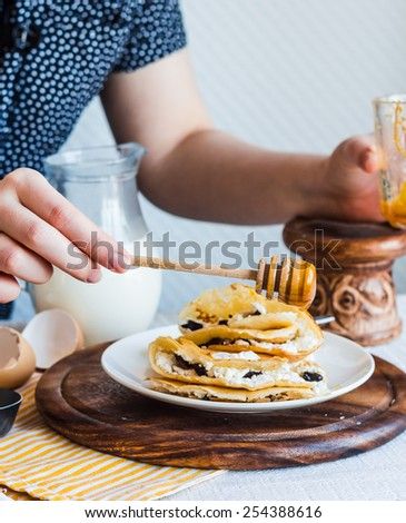 thin pancakes stuffed with cheese, prunes and sour cream, milk, add honey, hand, breakfast