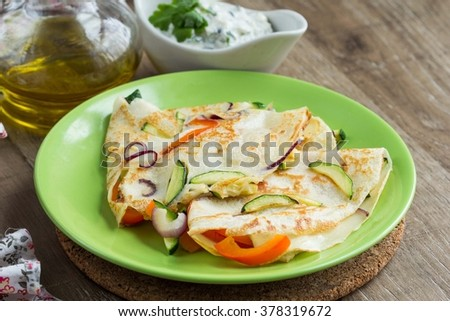 Thin pancakes stuffed with vegetables and Greek sauce, crepes on Shrove Tuesday - stock photo
