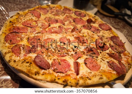 Thin peperoni pizza with melted cheese closeup