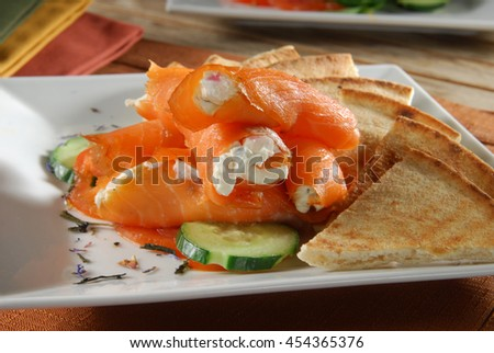 Thin sliced salmon stuffed with cream cheese and served on pita wedges - stock photo