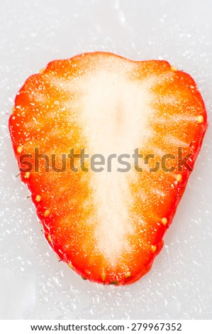 Thin sliced strawberry closeup on white background.