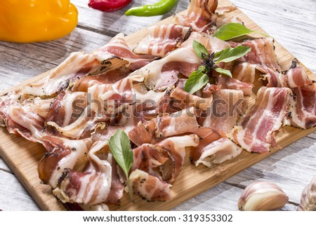 thin slices of bacon with freshly ground black pepper and basil on a wooden board with garlic, hot chili peppers, close-up, selective focus - stock photo