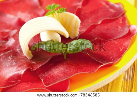 Thin slices of dry cured ham and butter - stock photo