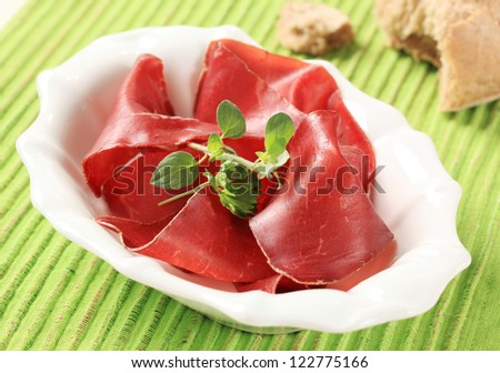 Thin slices of dry cured ham in a bowl  - stock photo