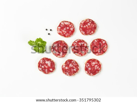thin slices of french dry salami, parsley and peppercorns on white background - stock photo