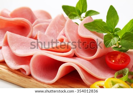 Thin slices of ham on cutting board - stock photo