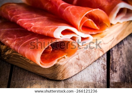 thin slices of prosciutto closeup on wooden cutting board - stock photo