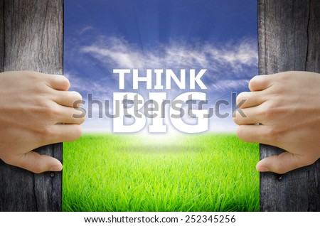 Thing Big motivational quotes. Hand opening an old wooden door and found a texts floating over green field and bright blue Sky Sunrise. - stock photo