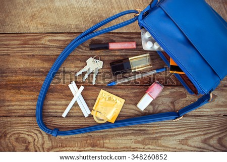 Things from open lady handbag. Cosmetics, female accessories, birth control pill, cigarette and condom falls out of pocket with handbags on wooden background. Toned image.  - stock photo