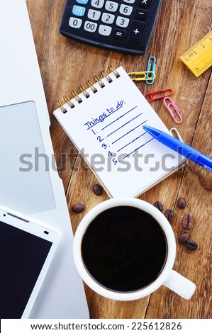 Things to do. Small notebook with text on table with coffee,calculator,notebook and other stationery. - stock photo