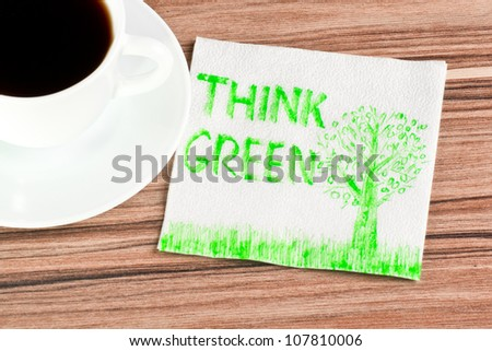 Think Green on a napkin and cup of coffee - stock photo