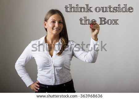 Think Outside the Box - Beautiful girl writing on transparent surface - horizontal image