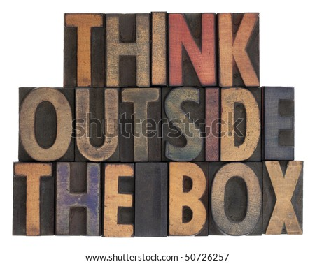 think outside the box phrase in vintage wooden letterpress type, stained by ink, isolated on white