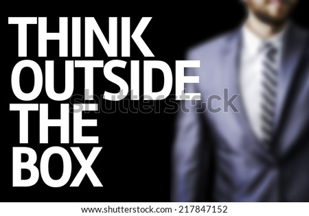 Think Outside The Box written on a board with a business man on background - stock photo