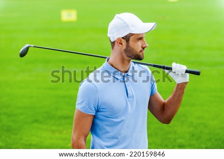 Thinking about next shot. Confident male golfer carrying driver on shoulder and looking away while standing on golf course - stock photo