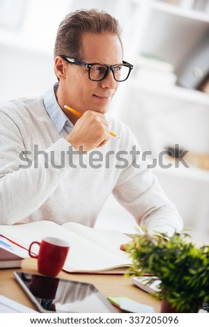 Thinking about solution. Thoughtful mature man holding hand on chin and looking away with smile while sitting at his working place - stock photo