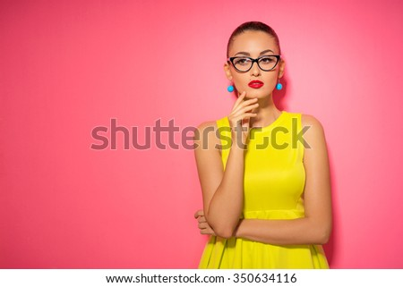 Thinking about solutions. Colorful studio portrait of thoughtful young woman in yellow dress holding hand on chin against pink wall. - stock photo