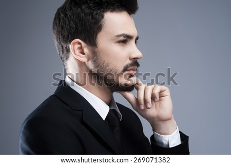 Thinking about solutions. Side view of thoughtful young man in formalwear looking away and holding hand on chin while standing against grey background - stock photo