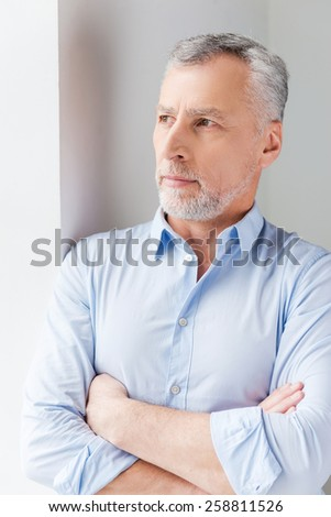Thinking about solutions. Thoughtful grey hair senior man in shirt looking away while standing near the window  - stock photo