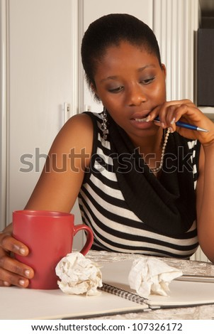 Thinking african woman writing a letter at home - stock photo