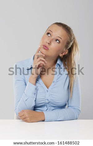 Thinking and pensive woman sitting at white desk
