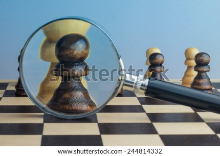 Thinking and strategy planning concept photography with chess pieces and magnifying glass. - stock photo