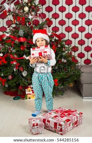 Thinking boy holding Christmas gift in front of tree
