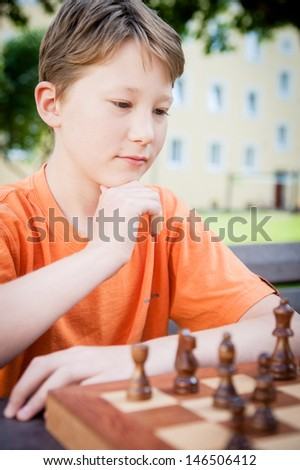 Thinking boy in a chess game - stock photo