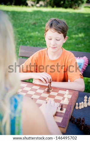 Thinking boy waiting for his next move in a chess game - stock photo