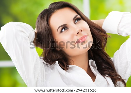 thinking brunette businesswoman looking up, with raised arms, at office - stock photo