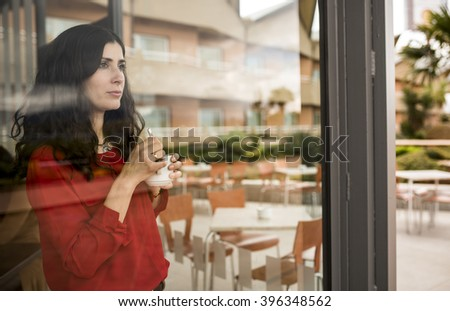 Thinking brunette standing in cafe behind window with cup of coffee while looking away