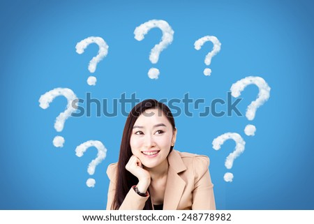 Thinking business asian woman looking up on many questions mark isolated on blue background