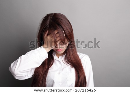 Thinking business woman isolated on grey background with finger at face, asian beauty - stock photo